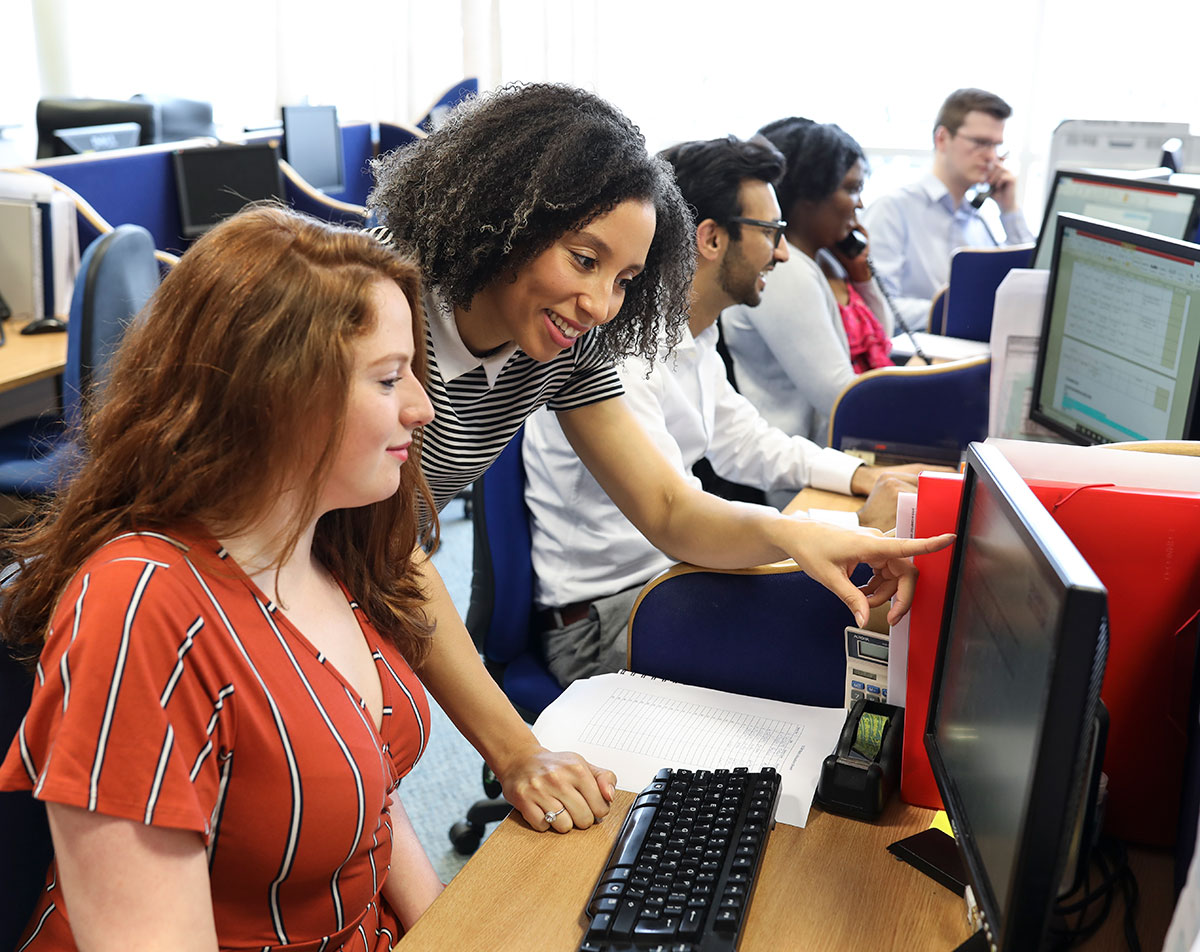 woman pointing at other woman's computer in charity response handling services
