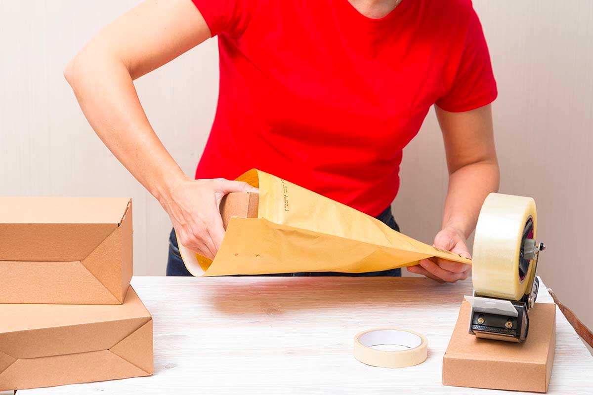 woman packing envelope in charity fulfilment service