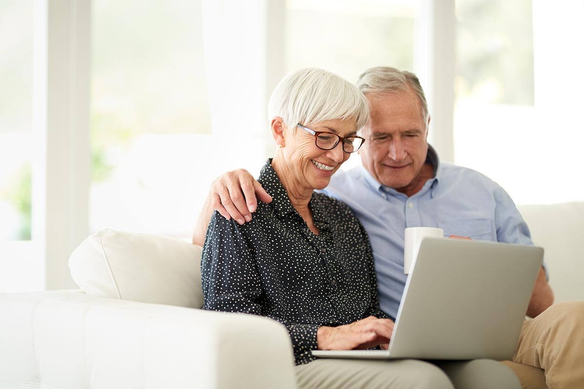 man and woman looking at laptop using charity membership services